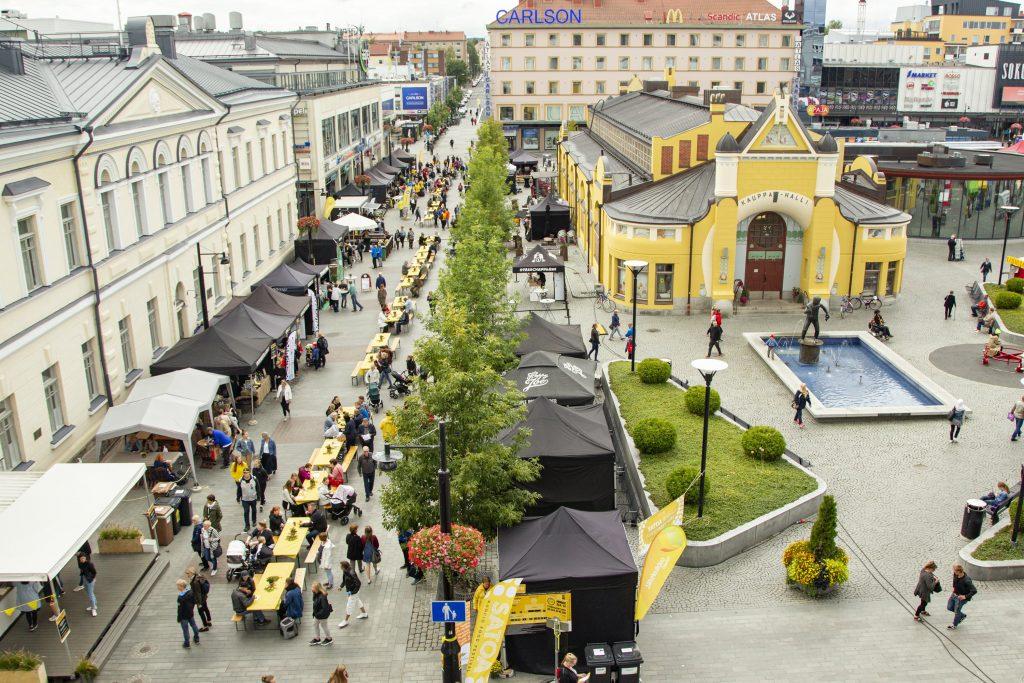 Ihmisiä ruokakojujen vieressä, Kuopion kauppahalli ja Veljmies-patsas