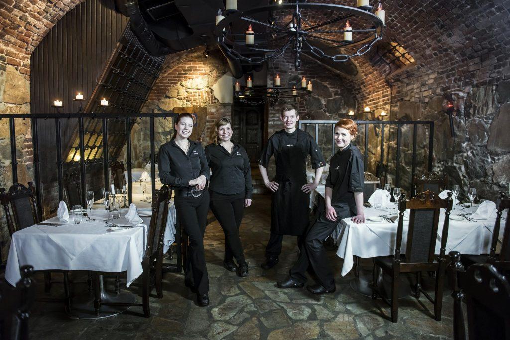 Ravintola Mustan Lampaan luolamaisessa tunnelmassa pöydät on katettu ja tarjoilijat ja kokit hymyilevät kameralle
